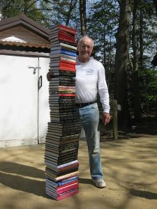 Roy F. Chandler standing next to a stack of the books he has written. Photo by Katherine R. Chandler/29 April 2009